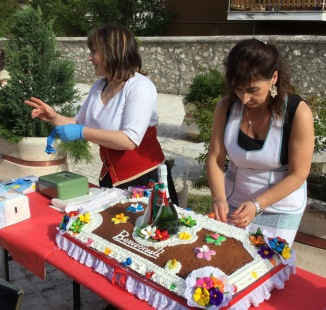 Ladies cutting il pizzillato, a traditional cake at Campo di Giove.